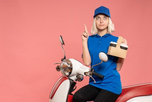 Vue de face femme courrier avec tasses à café sur le service de livraison rose travail travail uniforme de couleur travailleur