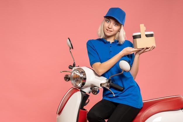Vue de face femme courrier avec des tasses à café sur le service de livraison rose travail travail uniforme de couleur