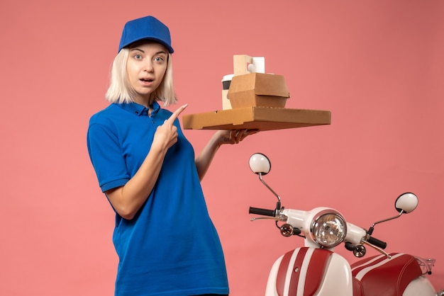 Vue de face femme courrier tenant boîte à pizza et café sur rose