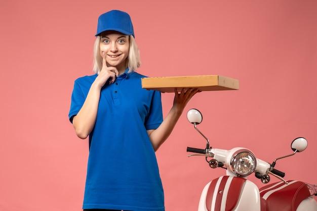 Vue de face femme courrier tenant boîte à pizza sur le rose