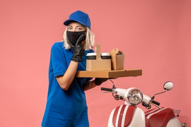 Vue de face femme courrier tenant des boîtes de nourriture sur le rose