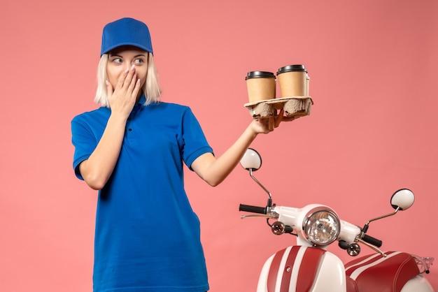 Vue de face femme courrier tenant le café de livraison sur le rose