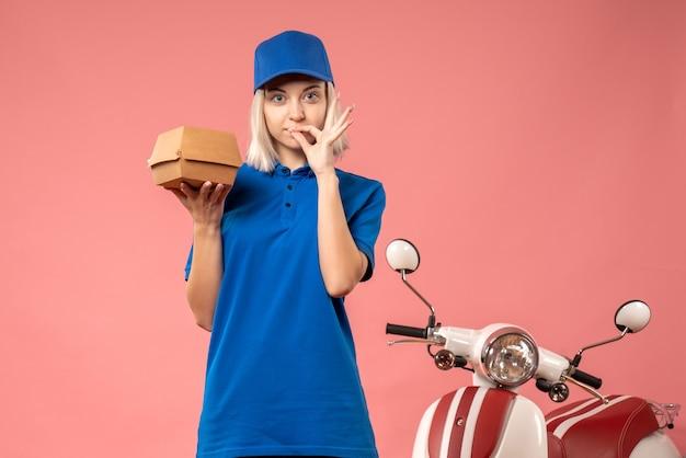 Vue de face femme courrier tenant petit paquet de nourriture sur rose