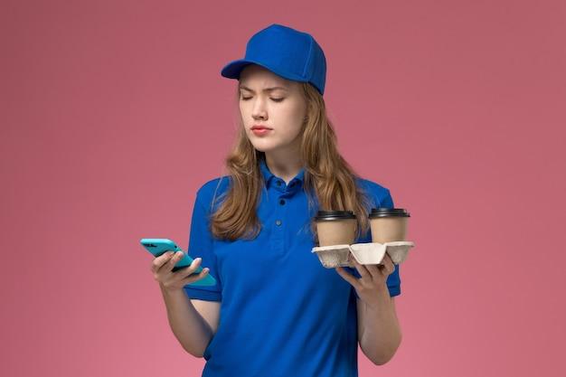 Vue de face femme courrier en uniforme bleu à l'aide de son téléphone tenant des tasses de café de livraison marron sur le bureau rose travail de l'entreprise uniforme de travail
