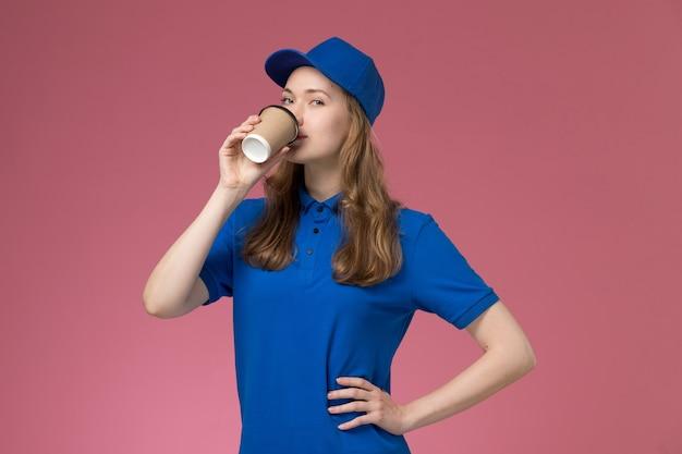 Vue de face femme courrier en uniforme bleu boire du café sur l'uniforme de service de bureau rose offrant un travail de l'entreprise