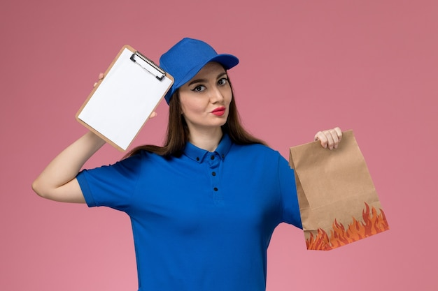 Vue de face femme courrier en uniforme bleu et cape tenant le bloc-notes et le paquet alimentaire papier pensée sur mur rose