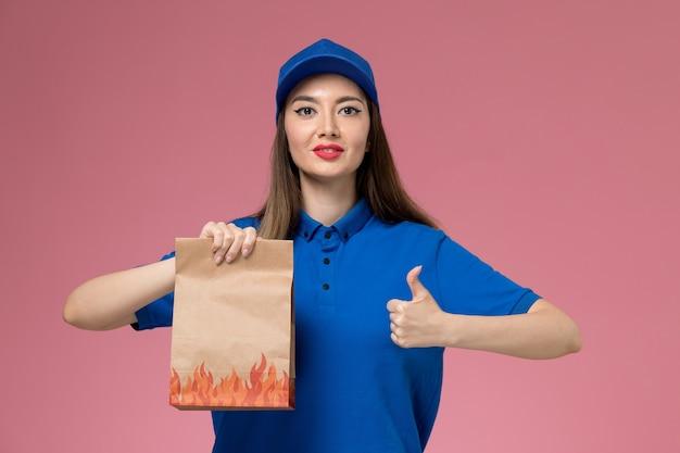 Vue de face femme courrier en uniforme bleu et cape tenant un paquet de papier alimentaire sur le mur rose