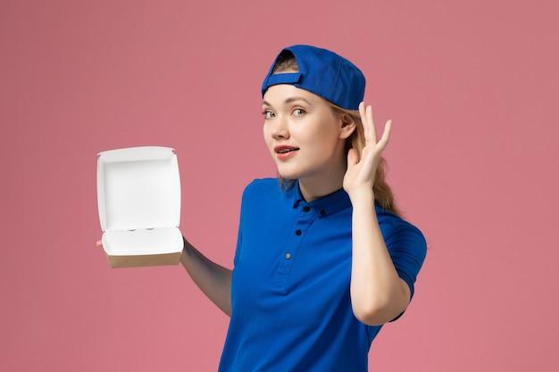 Vue de face femme courrier en uniforme bleu et cape tenant peu de colis de nourriture de livraison essayant d'entendre sur le mur rose, un employé de service de livraison uniforme