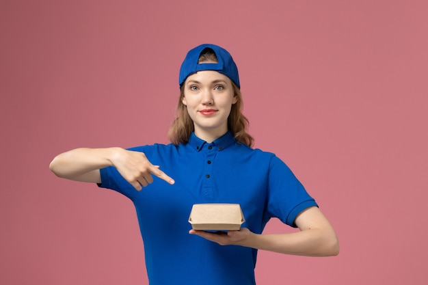 Vue de face femme courrier en uniforme bleu et cape tenant peu de colis de nourriture de livraison sur le fond rose service de livraison entreprise de travail travailleur