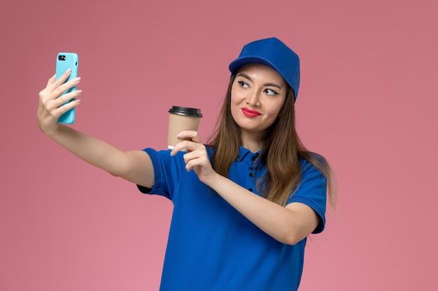 Vue de face femme courrier en uniforme bleu et cape tenant la tasse de café de livraison et prendre une photo avec elle sur le mur rose