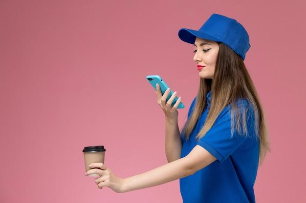 Vue de face femme courrier en uniforme bleu et cape tenant la tasse de café de livraison et en prendre une photo sur le mur rose