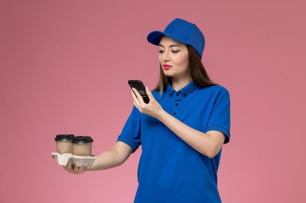 Vue de face femme courrier en uniforme bleu et cape tenant des tasses de café de livraison en prenant une photo d'eux sur le mur rose