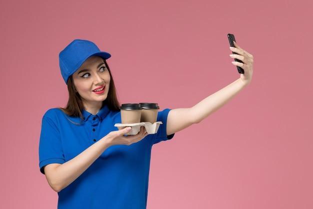 Vue de face femme courrier en uniforme bleu et cape tenant des tasses de café de livraison en prenant une photo sur le mur rose