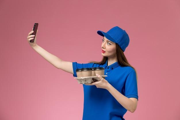 Vue de face femme courrier en uniforme bleu et cape tenant des tasses à café en prenant une photo sur le mur rose