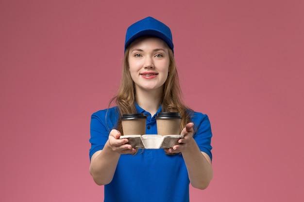 Vue de face femme courrier en uniforme bleu offrant des tasses de café marron sur l'uniforme de service de bureau rose offrant des emplois de l'entreprise