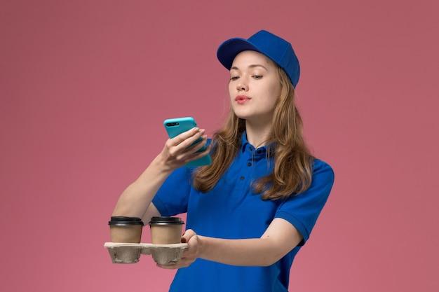 Vue de face femme courrier en uniforme bleu en prenant une photo de la livraison des tasses de café sur le travail de l'entreprise uniforme de bureau lumière rose
