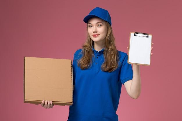 Vue de face femme courrier en uniforme bleu tenant la boîte de livraison de nourriture et le bloc-notes sur le service de bureau rose travailleur de l'entreprise uniforme