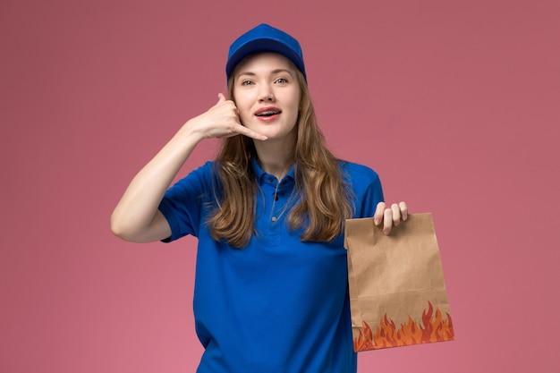 Vue de face femme courrier en uniforme bleu tenant le paquet alimentaire montrant le geste d'appel téléphonique sur le bureau rose entreprise uniforme de service des travailleurs
