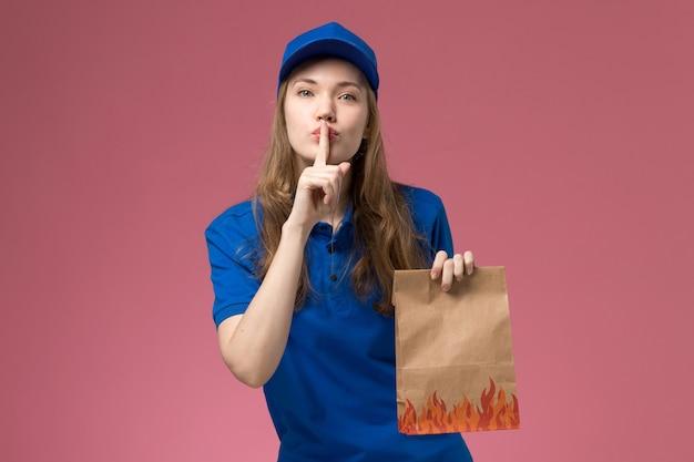 Vue de face femme courrier en uniforme bleu tenant le paquet alimentaire montrant le silence signe sur le bureau rose entreprise uniforme de service des travailleurs