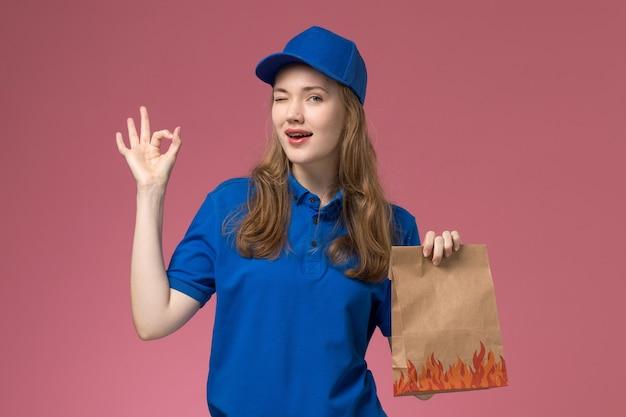 Vue de face femme courrier en uniforme bleu tenant le paquet alimentaire souriant et un clin de œil sur le bureau rose clair entreprise uniforme de service des travailleurs