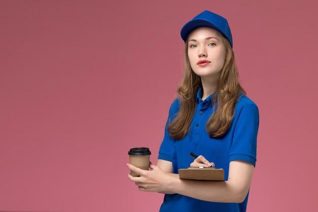 Vue de face femme courrier en uniforme bleu tenant une tasse de café marron avec bloc-notes sur le bureau de service de bureau rose clair qui offre un uniforme