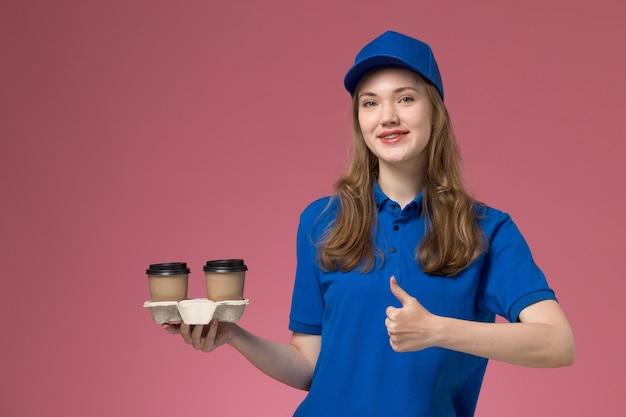 Vue de face femme courrier en uniforme bleu tenant des tasses de café brun posant et souriant sur l'uniforme de service de fond rose offrant des emplois de l'entreprise