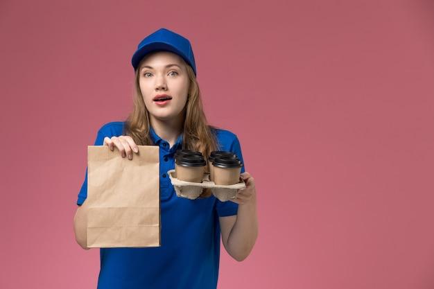 Vue de face femme courrier en uniforme bleu tenant des tasses de café de livraison marron avec emballage alimentaire sur le service de bureau rose clair travailleur de l'entreprise uniforme