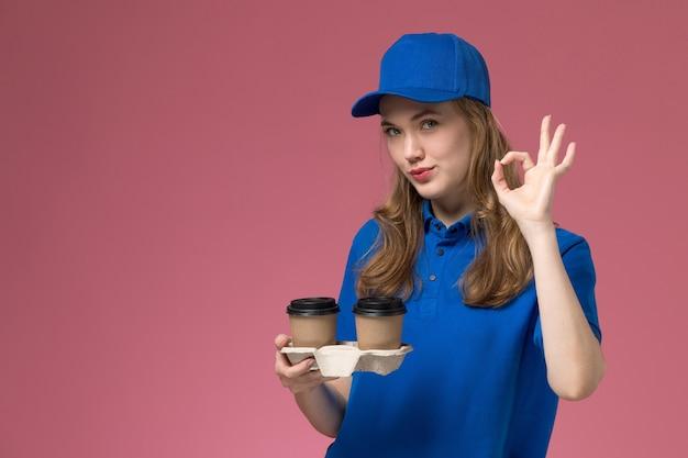 Vue de face femme courrier en uniforme bleu tenant des tasses de café marron montrant bien sourire sur l'uniforme de service de fond rose offrant des emplois