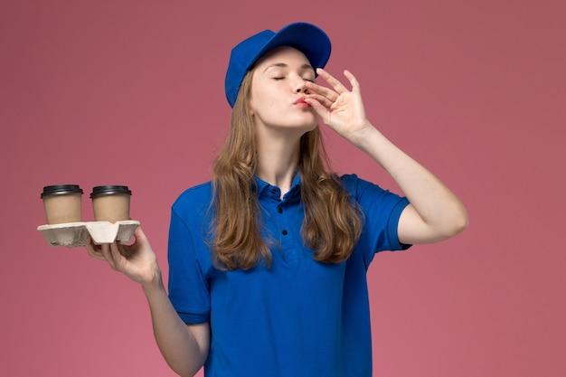 Vue de face femme courrier en uniforme bleu tenant des tasses de café marron montrant le goût signe sur l'uniforme de service de fond rose offrant des emplois de l'entreprise