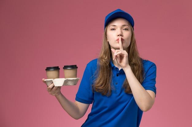 Vue de face femme courrier en uniforme bleu tenant des tasses de café marron montrant le signe de silence sur l'uniforme de service de bureau rose offrant des emplois de l'entreprise