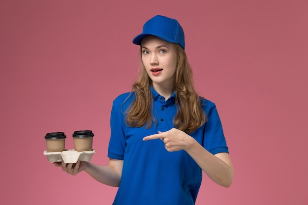 Vue de face femme courrier en uniforme bleu tenant des tasses de café marron posant sur l'uniforme de service de bureau rose offrant des emplois de l'entreprise