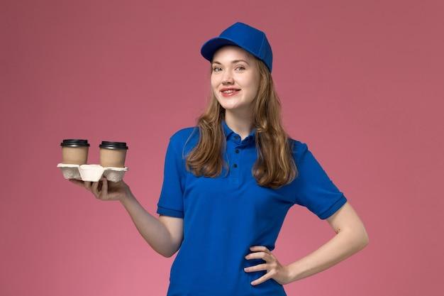 Vue de face femme courrier en uniforme bleu tenant des tasses de café marron sur l'uniforme de service de bureau rose offrant des emplois de l'entreprise
