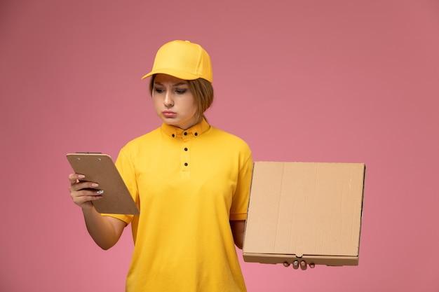 Vue de face femme courrier en uniforme jaune cape jaune tenant le bloc-notes de la boîte alimentaire sur le bureau rose femme de livraison uniforme