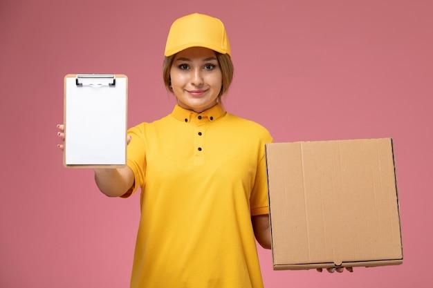 Vue de face femme courrier en uniforme jaune cape jaune tenant le bloc-notes boîte alimentaire sur le plancher rose livraison uniforme couleur féminine