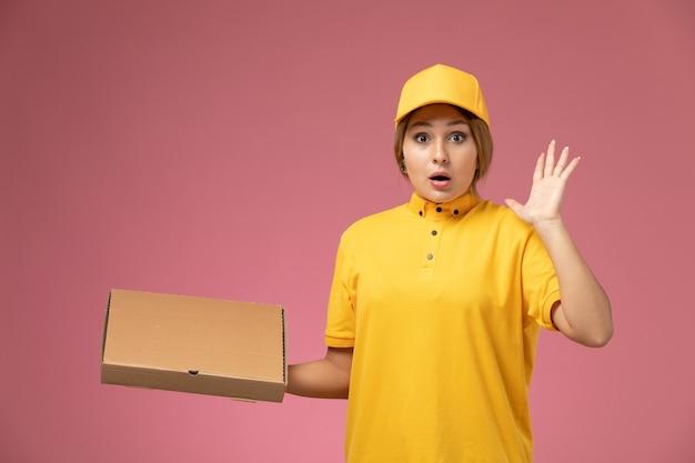 Vue de face femme courrier en uniforme jaune cape jaune tenant la boîte de livraison de nourriture sur le bureau rose couleur femelle de livraison uniforme