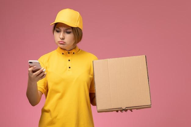Vue de face femme courrier en uniforme jaune cape jaune tenant la boîte de nourriture à l'aide de son téléphone sur le bureau rose couleur féminine de livraison uniforme