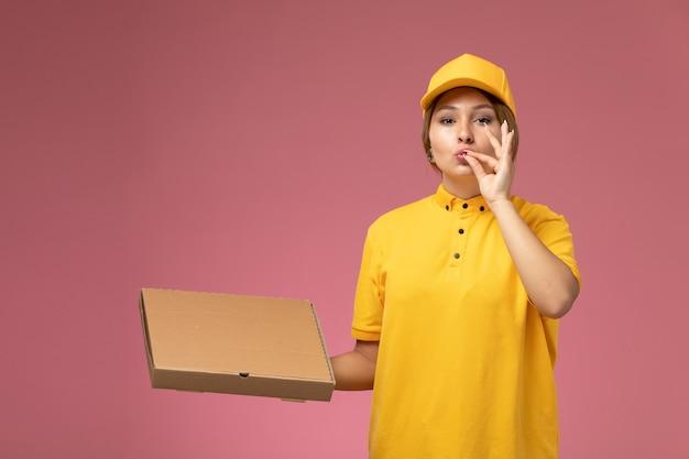 Vue de face femme courrier en uniforme jaune cape jaune tenant la boîte de nourriture sur la livraison de travail uniforme de bureau rose couleur féminine