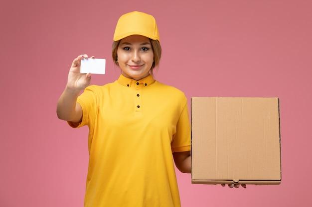Vue de face femme courrier en uniforme jaune cape jaune tenant une carte blanche et une boîte de nourriture sur le bureau rose couleur féminine de livraison uniforme