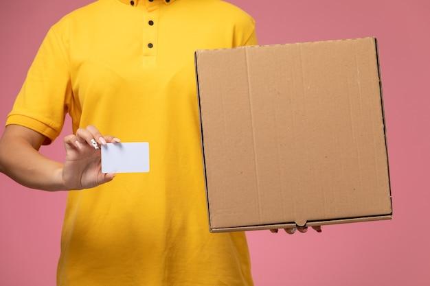 Vue de face femme courrier en uniforme jaune cape jaune tenant une carte blanche avec boîte de nourriture sur le bureau rose livraison uniforme couleur féminine