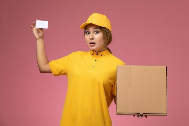 Vue de face femme courrier en uniforme jaune cape jaune tenant une carte en plastique et une boîte de nourriture sur le bureau rose livraison uniforme couleur féminine