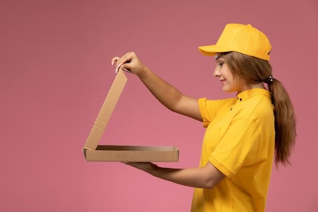 Vue de face femme courrier en uniforme jaune cape jaune tenant le colis de livraison avec sourire sur le travail de travail de livraison uniforme fond rose