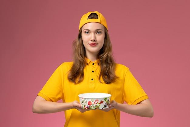 Vue de face femme courrier en uniforme jaune et cape tenant le bol de livraison sur le mur rose service de livraison de l'entreprise uniforme