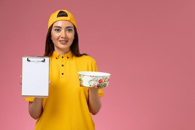 Vue de face femme courrier en uniforme jaune et cape tenant un bol de livraison rond avec bloc-notes sur le mur rose service travail de livraison uniforme