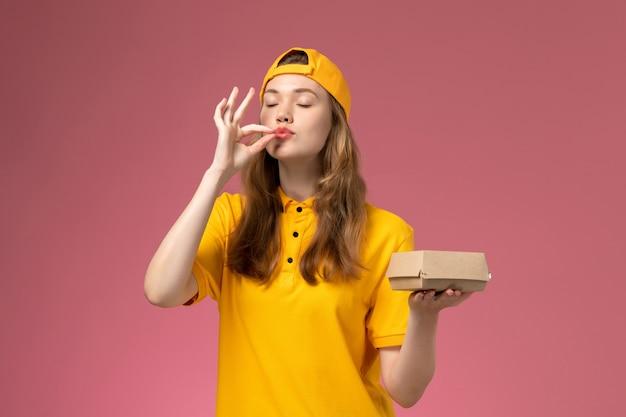 Vue de face femme courrier en uniforme jaune et cape tenant le paquet de nourriture de livraison sur le mur rose service de livraison de travail uniforme