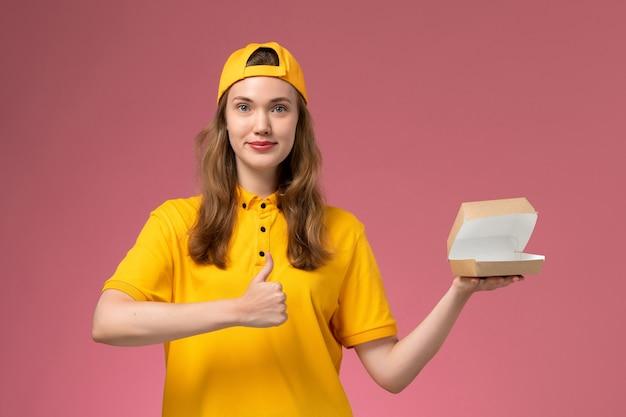 Vue de face femme courrier en uniforme jaune et cape tenant un petit paquet de nourriture de livraison vide sur l'uniforme de livraison de service de mur rose clair