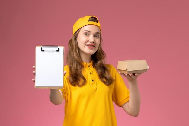 Vue de face femme courrier en uniforme jaune et cape tenant peu de colis alimentaires de livraison et bloc-notes sur mur rose clair service de livraison de travail uniforme