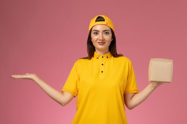 Vue de face femme courrier en uniforme jaune et cape tenant peu de colis alimentaires de livraison sur un mur rose clair entreprise de livraison de services d'emploi uniforme