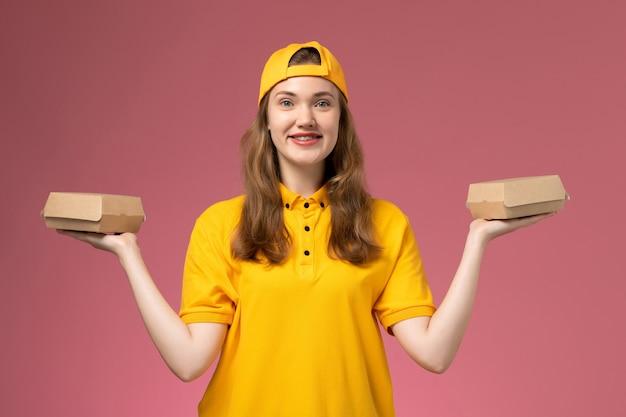 Vue de face femme courrier en uniforme jaune et cape tenant peu de colis alimentaires de livraison sur le mur rose service travail travail de livraison uniforme