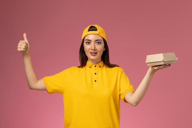 Vue de face femme courrier en uniforme jaune et cape tenant peu de colis de nourriture de livraison sur le mur rose travailleur de la livraison de services uniforme