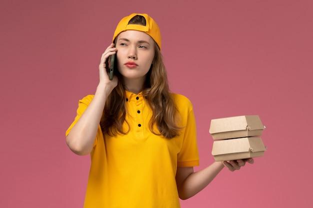 Vue de face femme courrier en uniforme jaune et cape tenant le téléphone avec des emballages alimentaires sur l'uniforme de livraison de services de l'entreprise travailleur mural rose